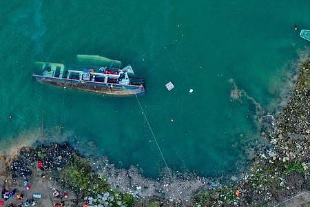 Das gekenterte Schiff im Zangke-Fluss. Foto: Ou Dongqu/XinHua/dpa