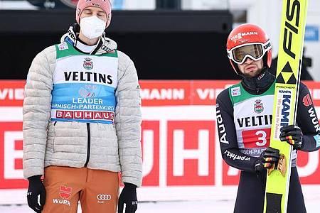 Karl Geiger und Markus Eisenbichler (r) liegen vor dem letzten Springen hinter den Podestplätzen. Foto: Daniel Karmann/dpa