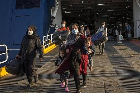 Flüchtlinge aus dem kürzlich ausgebrannten Lager Moria auf Lesbos und anderen griechischen Inseln verlassen eine Fähre im Hafen von Lavrio bei Athen. Foto: Socrates Baltagiannis/dpa