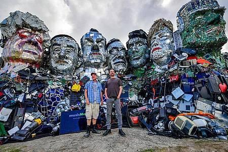 Die Künstler Alex Wreckage (l) und Joe Rush von der «Mutoid Waste Company» stehen vor dem G7-Gipfel in Cornwall vor ihrem Kunstwerk «Mount Trashmore» am Strand bei Gwithian. Foto: Ben Birchall/PA Wire/dpa