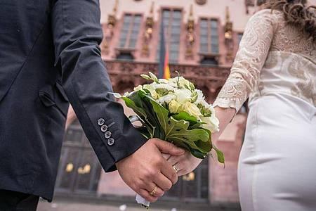 Ein Brautpaar steht nach der standesamtlichen Trauung auf dem Römerberg in Frankfurt. Foto: Frank Rumpenhorst/dpa