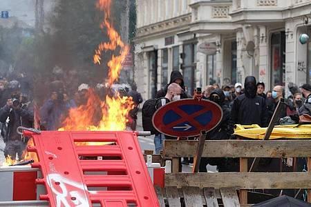 Maskierte Demo-Teilnehmer stehen hinter einer Barrikade. Foto: Sebastian Willnow/dpa-Zentralbild/dpa