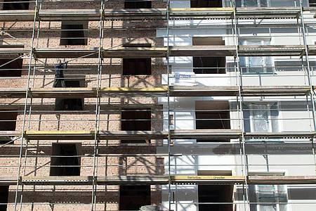 An einem Altbau wird mit Hilfe eines Baugerüstes während der Renovierung des Hauses eine Wärmedämmung an die Fassade angebracht. Foto: Arno Burgi/dpa-Zentralbild/dpa