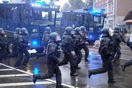 Polizisten laufen über eine Kreuzung im Leipziger Stadtteil Connewitz. Foto: Sebastian Willnow/dpa-Zentralbild/dpa