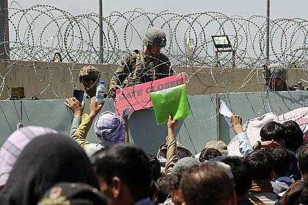 Hunderte von Menschen in der Nähe eines Evakuierungskontrollpunkts auf dem Gelände des Flughafens Kabul. Dort hatte es zuvor einen Anschlag mit mehreren Toten gegeben. Foto: AP/dpa