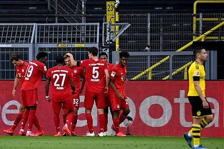 Die Bayern-Spieler feiern in Dortmund den Matchwinner Joshua Kimmich (M). Foto: Federico Gambarini/dpa-Pool/dpa