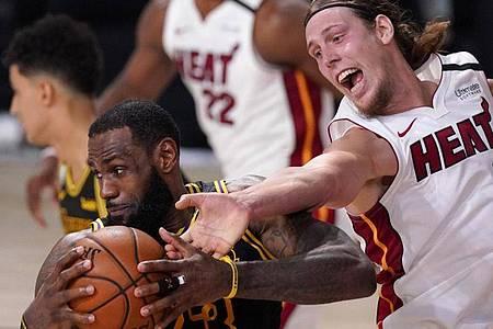 LeBron James (l/23) von den Los Angeles Lakers setzt sich gegen Kelly Olynyk (r/9) von Miami Heat durch. Foto: Mark J. Terrill/AP/dpa