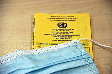 Gelber Impfpass mit Mundschutz