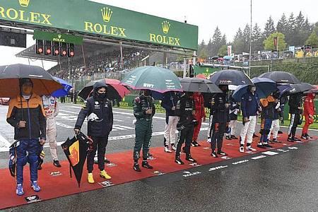 Die Fahrer stehen vor dem Start zusammen im Regen. Foto: John Thys/Pool AFP/AP/dpa