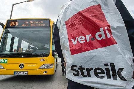 Ein streikender Busfahrer steht in Regensburg vor einem Bus. Foto: picture alliance / dpa
