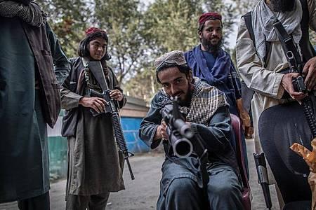 Ein junger Taliban-Kämpfer zielt zum Spaß mit seinem Gewehr in Richtung Fotograf, während er vor einer Polizeistation in Kabul Wache hält. Foto: Oliver Weiken/dpa