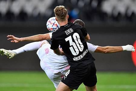 Karim Benzema (l) brachte Real Madrid mit seinem Tor wieder zurück ins Spiel. Foto: Marius Becker/dpa