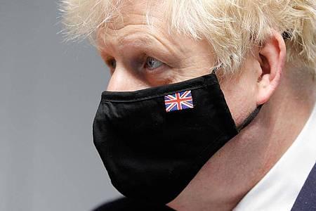 Premier Boris Johnson trägt einen Mund-Nasen-Schutz mit dem Union Jack. Foto: Phil Noble/PA Wire/dpa