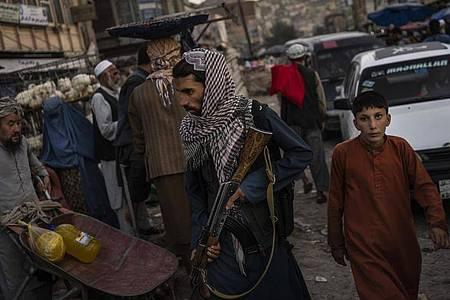 Ein Taliban-Kämpfer patrouilliert auf einem Markt in Kabul (Symbolbild). Foto: Bernat Armangue/AP/dpa