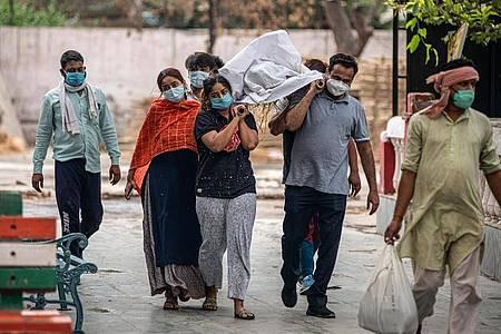 Verwandte tragen im indischen Ghazipur die Leiche eines Angehörigen auf den Einäscherungsplatz. Foto: Pradeep Gaur/SOPA Images via ZUMA Wire/dpa