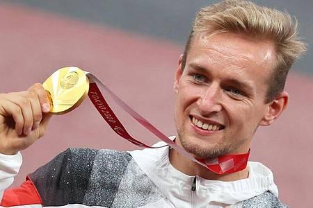 Johannes Floors hält bei der Siegerehrung seine Goldmedaille hoch. Foto: Karl-Josef Hildenbrand/dpa