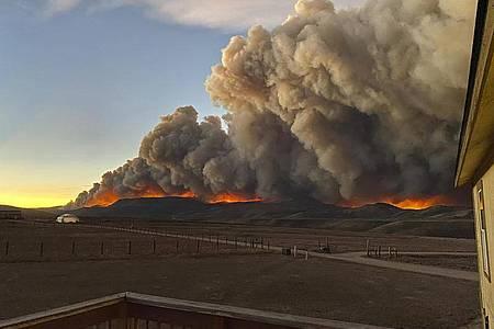 Flammen und aufsteigende Rauchwolken hinter einem Bergkamm im Rocky Mountain Nationalpark. Foto: Jessy Ellenberger/AP/dpa