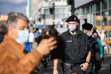 Bundespolizisten kontrollieren auf einer Einkaufsstraße in Berlin die Einhaltung der Maskenpflicht. Foto: Christoph Soeder/dpa