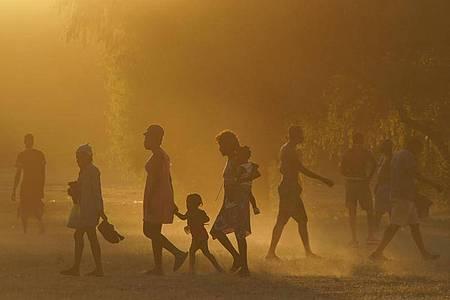 Migranten, viele von ihnen aus Haiti, gehen zu einem improvisierten Flüchtlingslager in Ciudad Acuña. Foto: Fernando Llano/AP/dpa