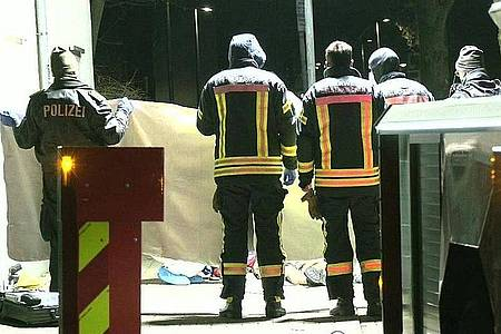 Feuerwehrleute errichten am Tatort einen Sichtschutz. Foto: Michael Weber/Wtvnews/dpa