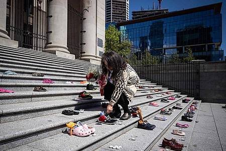 Eine Angehörige einer indigenen Volksgruppe legt eine Rose auf eines von 215 Paar Kinderschuhen auf den Stufen der Vancouver Art Gallery. Foto: Darryl Dyck/The Canadian Press via ZUMA/dpa