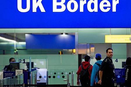 Grenzbeamte stehen am Flughafen Heathrow in London unter einem Schild mit der Aufschrift «UKBorder». Foto: Andrew Cowie/EPA/dpa
