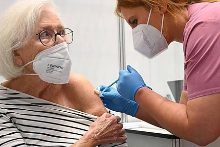 Claudia Kreil (r) vom Impfzentrum am Robert-Bosch-Krankenhaus inStuttgart verabreicht einer Patientin die Auffrischimpfung gegen das Coronavirus. Foto: Bernd Weißbrod/dpa