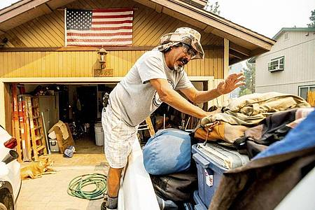 Michael Posadas bereitet sich nahe des Lake Tahoe auf die Evakuierung vor. Das beliebte kalifornische Ausflugsgebiet ist von schnell um sich greifenden Waldbränden bedroht. Foto: Noah Berger/AP/dpa