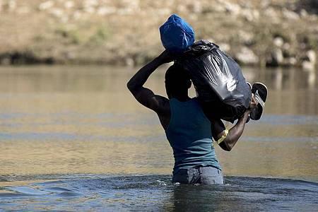 Ein haitianischer Migrant versucht den Fluss Rio Grande von Mexiko in die USA zu überqueren. Foto: Nick Wagner/XinHua/dpa