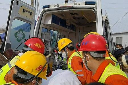 Retter tragen einen geretteten Bergarbeiter zu einem Krankenwagen. Zwei Wochen nach einem Grubenunglück im Osten Chinas wurde er geborgen. Foto: Luan Qincheng/XinHua/dpa