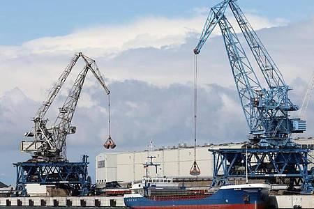 Im Seehafen an der Ostsee wird ein Schiff mit Kränen abgefertigt. Foto: Bernd Wüstneck/dpa-Zentralbild/dpa