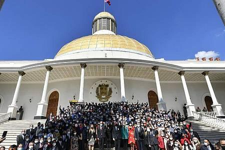 Die Abgeordneten stehen zusammen auf den Stufen der Nationalversammlung, nachdem sie vereidigt wurden. Foto: Matias Delacroix/AP/dpa
