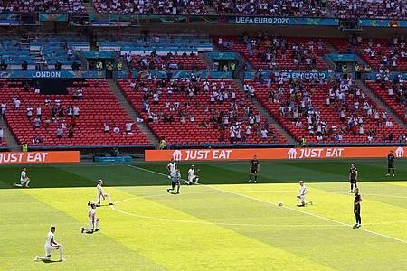 Die Spieler von England knien vor Spielbeginn auf dem Rasen. Foto: Martin Rickett/PA Wire/dpa