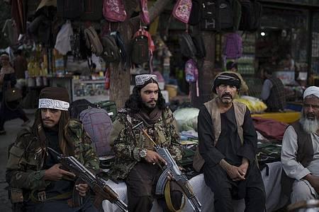 Taliban-Kämpfer sitzen neben Straßenverkäufern auf einem lokalen Markt und halten dabei Waffen in den Händen. Foto: Felipe Dana/AP/dpa