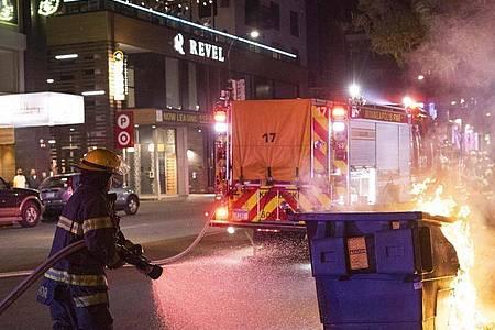 Wütende Menschen, brennende Mülltonnen: Erneut ist in Minneapolis eine Polizeiaktion tödlich eskaliert - hier war vor einem Jahr der Afroamerikaner George Floyd bei einem Einsatz ums Leben gekommen. Foto: Christian Monterrosa/FR171731 AP/dpa