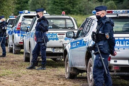 Polizeibeamte stehen an der polnisch-belarussischen Grenze. Foto: Attila Husejnow/SOPA Images via ZUMA Press Wire/dpa