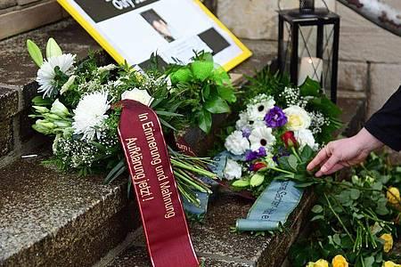 Teilnehmer einer Mahnwache haben zum Gedenken an Oury Jalloh Blumen und Kerzen an einer Treppe vor dem Polizeirevier in Dessau-Roßlau niedergelegt. Foto: Hendrik Schmidt/dpa-Zentralbild/dpa