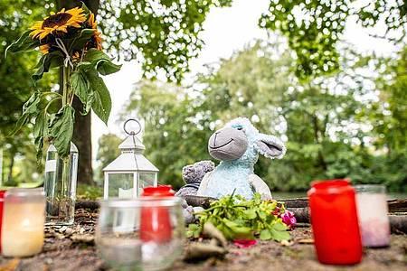 Zwei Stofftiere, Kerzen und Sonnenblumen sind an dem kleinen See in Hamm abgelegt worden. Foto: Guido Kirchner/dpa