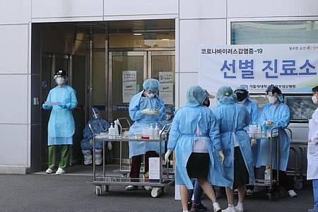 Medizinisches Personal in Schutzausrüstung steht vor einem Krankenhaus in Südkorea. Foto: -/YNA/dpa