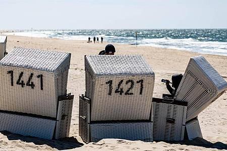 Ein Mann sitzt am Strand von Sylt in einem Strandkorb. Die Urlaubsorte an Nord- und Ostsee in Schleswig-Holstein sind über das Pfingstwochenende gut gebucht. Foto: Axel Heimken/dpa