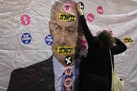 Ein Plakat mit dem Konterfei von Israels Premierminister Netanjahu wird mit Aufklebern überklebt. Foto: Sebastian Scheiner/AP/dpa