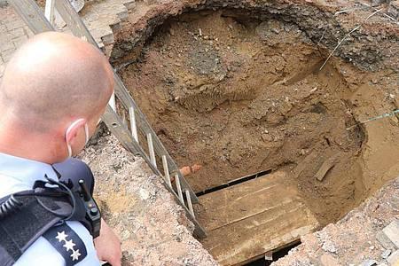 Ein Polizist schaut auf das Loch eines Tunnels, den Unbekannte zur Volksbank gegraben haben. Foto: Ekkehard Wind/dpa