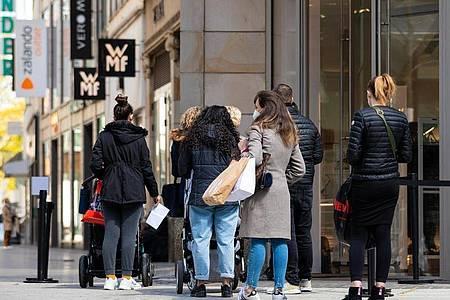 Menschen warten vor einem Geschäft in der Hannoveraner Innenstadt auf Einlass. Foto: Moritz Frankenberg/dpa