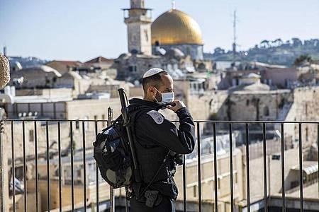 Ein israelischer Polizist mit Mundschutz steht in der Altstadt Wache, im Hintergrund der Felsendom auf dem Tempelberg. (zu dpa: «Tempelberg nach Waffenruhe wieder für Juden geöffnet»). Foto: Ilia Yefimovich/dpa