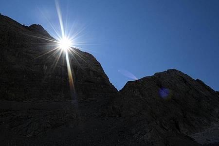 Die Sonne kommt am Morgen hinter einem Felsen im Watzmannkar (Bayern) hervor. Foto: Angelika Warmuth/dpa