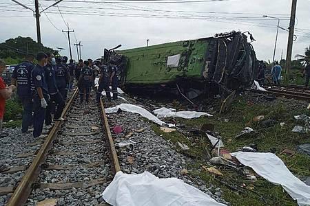 Rettungskräfte stehen an einem beschädigten Zug und neben mit weißen Tüchern bedeckten Leichen. Mindestens 17 Menschen sind am Sonntag in Thailand beim Zusammenstoß eines Busses mit einem Zug ums Leben gekommen. Foto: Uncredited/Daily News/AP/dpa