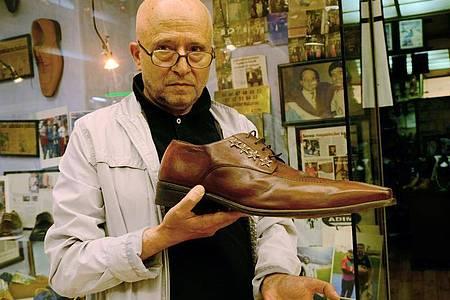 Schuster Öncel Kalkan zeigt vor seinem Laden den größten Schuh, den er produziert hat - er ist 57 Zentimeter lang. Foto: Anne Pollmann/dpa