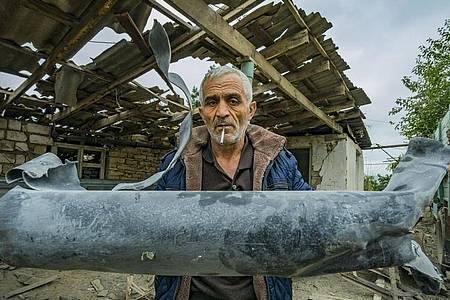 Ein Mann zeigt die Reste einer Rakete, die sein Haus im armenischen Martuni zerstört hat. Foto: Celestino Arce Lavin/ZUMA Wire/dpa