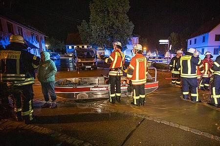 Feuerwehrleute im Kreis Biberach stehen neben einem Feuerwehrboot auf einer Straße in den Fluten eines heftigen Unwetters. Foto: Simon Adomat/VMD Images/dpa