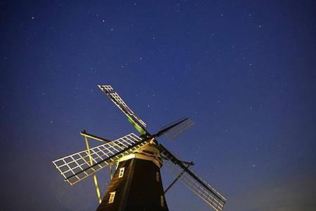 Der Sternenhimmel über der Nordermühle auf der Insel Pellworm. Foto: Marcus Brandt/dpa